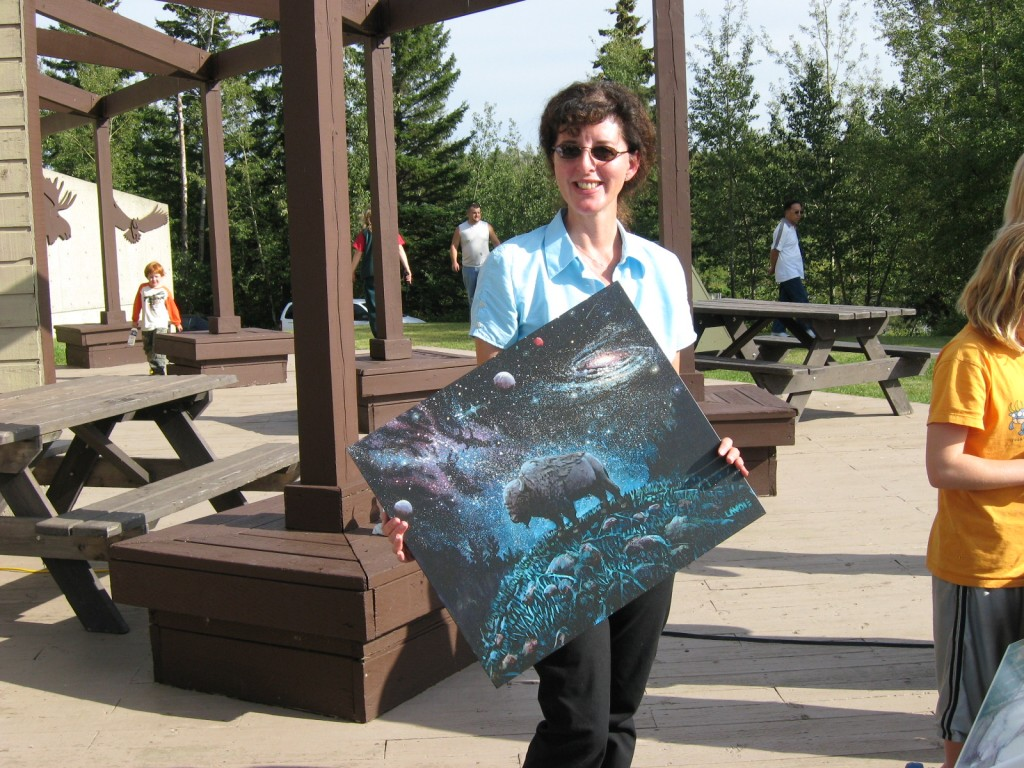 """The better looking author poses with her Lewis Lavois """"Dark Skies"""" painting, presented in appreciation of her work in the creation of the DSP. Image credit: Kathleen Houston"""